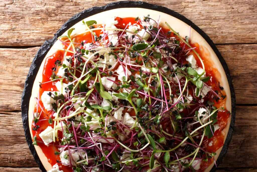 Microgreens on a pizza with tomato and feta cheeze